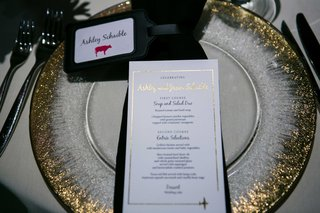 a-couples-dinner-menu-next-to-place-card-with-small-pink-cow-gold-rimmed-charger-plate