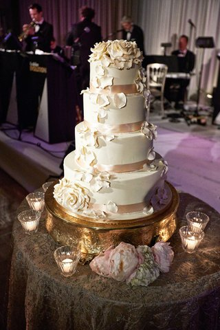 white-four-tier-wedding-cake-with-sugar-flowers-petals-and-pink-ribbon