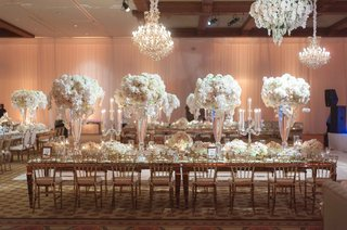 long-reception-table-in-ballroom-with-tall-centerpieces-chandeliers-mirror-details-candelabra