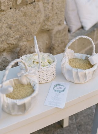 outdoor-wedding-white-baskets-filled-with-flower-petals-and-dried-rice-ceremony-program-with-wreath