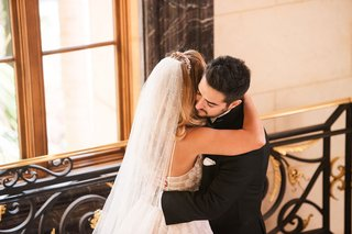 bride-and-groom-hug-after-first-look-at-hotel-bridal-veil-and-headpiece-crystal-flowers