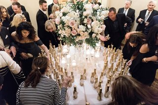 wedding-guests-looking-for-their-names-on-escort-card-tags-attached-to-miniature-champagne-bottles