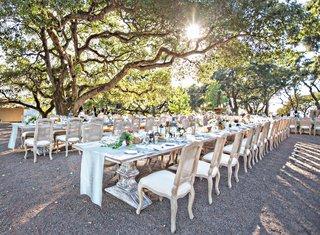 wedding-reception-long-tables-rustic-chairs-low-centerpiece-succulents-flowers-fruit-lanterns-sun