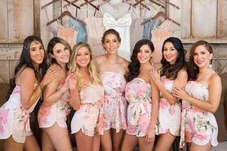 bride-with-bridesmaids-in-matching-flower-print-strapless-romper-shorts-in-front-of-bridesmaid-dress