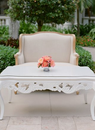 wedding-cocktail-hour-white-coffee-table-ornate-legs-pink-coral-flowers-settees-courtyard-cocktails