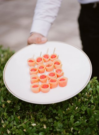 wedding-reception-hors-doeuvres-appetizer-held-over-green-hedge-by-server