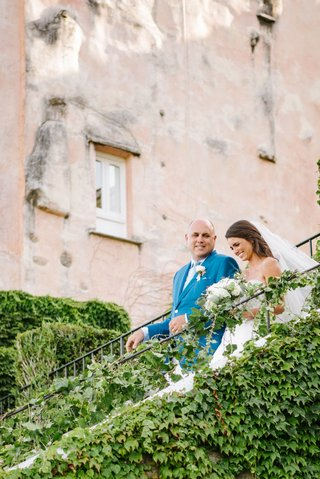 bride-in-veil-and-wedding-dress-walking-down-steps-vine-covered-staircase-with-dad-in-blue-jacket