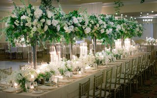 wedding-reception-head-table-with-tall-centerpieces-heavy-greenery-white-flowers
