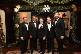 groom-with-dad-and-groomsmen-in-front-of-christmas-decorations