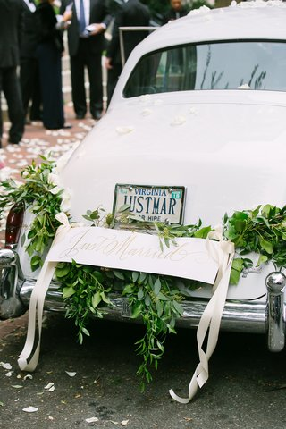 wedding-car-white-with-garland-of-greenery-and-just-married-sign-tied-with-ribbon-virginia-license