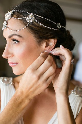 bride-putting-on-earrings-french-manicure-headdress-of-jewels-and-flower-details