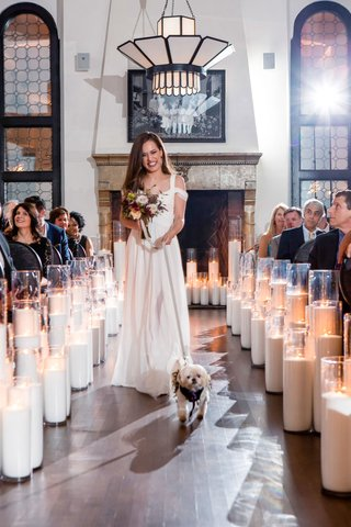 bridesmaid-in-off-shoulder-white-bridesmaid-dress-fall-bouquet-walking-little-dog-down-aisle-candles