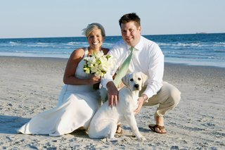 bride-and-groom-on-beach-with-white-lab-puppy