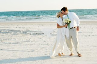 bride-and-groom-kiss-on-sand-at-beach-wedding