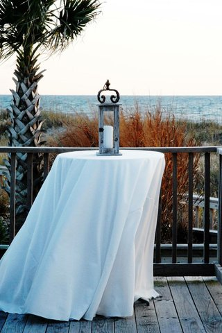 white-cocktail-table-with-wooden-lantern-next-to-ocean