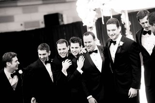 black-and-white-photo-of-groomsmen-smiling-in-tuxedos-and-bow-ties