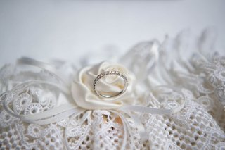 wedding ring on ring pillow white ribbon lace and flower silk design pave diamonds