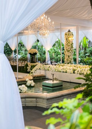 white-drapes-wedding-ceremony-space-with-fountain-white-rose-greenery-gold-chairs