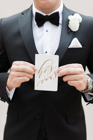groom-in-tuxedo-and-bow-tie-white-pocket-square-and-boutonniere-holding-his-vows-calligraphy-book