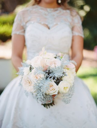 bride-holding-wintry-bouquet-of-verdure-berries-and-roses-in-shades-of-white-and-pale-pink