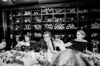 black-white-photo-of-bride-in-dark-dress-groom-in-suit-with-guests-at-del-pasto-wine-cellar