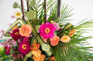 shower-head-lotus-seeds-pink-flowers-yellow-centers-orange-yellow-roses-palms-tropical-centerpiece