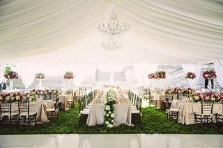 tented-wedding-reception-grass-long-rectangular-tables-flower-runner-and-tall-pink-centerpieces