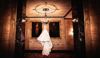 wedding-dress-hanging-from-chandelier-next-to-paintings