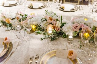 a-long-floral-table-runner-with-white-pink-and-orange-flowers-next-to-gold-charger-plates