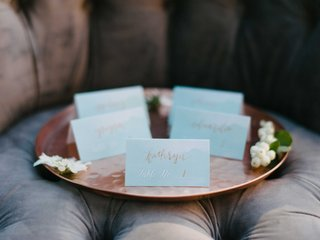 small-blue-escort-cards-with-rose-gold-calligraphy-on-a-rose-gold-serving-platter-on-a-brown-chair