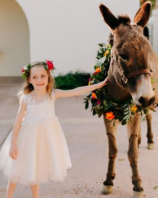 wedding at la quinta resort and club donkey with wreath of flowers flower girl blush dress pink ranunculus crown