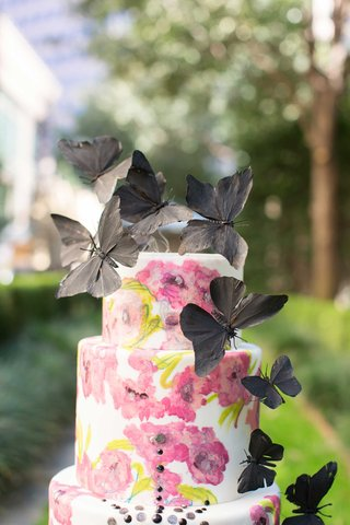 white-cake-with-pink-flower-design-and-black-jewels-and-black-butterflies-on-top