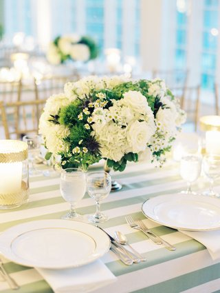 wedding reception green white stripe linen centerpiece with white rose hydrangea chamomile and moss thistle