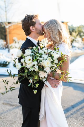 groom-in-brooks-brothers-tuxedo-kisses-bride-on-forehead-loosely-structured-bouquet