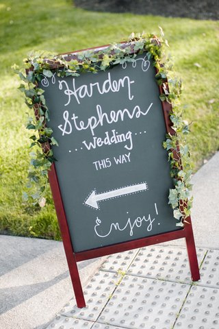 ivy-around-chalkboard-sign-at-wedding-entrance