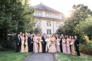 bride-and-groom-with-groomsmen-in-tuxes-and-bridesmaids-in-gold-and-pink-dresses-flower-girl
