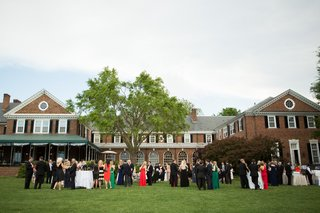 wedding-guests-on-grass-lawn-in-front-of-brick-country-club