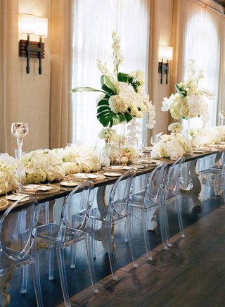 long-head-table-with-wood-top-high-and-low-tropical-centerpieces-ghost-chairs