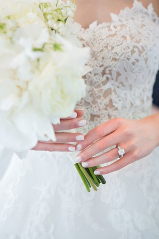 bride-with-pretty-manicure-holding-white-bouquet-emerald-cut-diamond-engagement-ring-side-stones