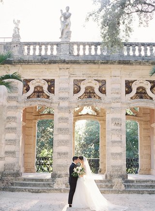 bride-in-wedding-dress-groom-in-tuxedo-in-front-of-villa-grounds-vizcaya-museum-and-gardens-in-miami