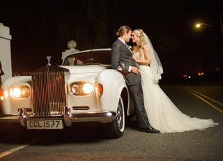 groom-in-grey-suit-and-bride-in-white-dress-on-english-luxury-car