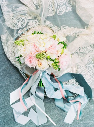 bouquet-of-pink-cream-white-flowers-greenery-on-lace-fabic-with-pink-blue-fabric-streamers