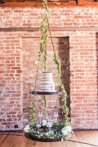 semi-naked-cake-on-tiered-display-suspended-from-ceiling-greenery-white-roses-floating-candles