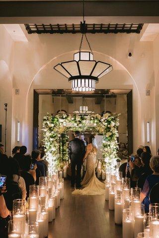 wedding-ceremony-hotel-figueroa-candles-lining-aisle-greenery-white-flower-chuppah