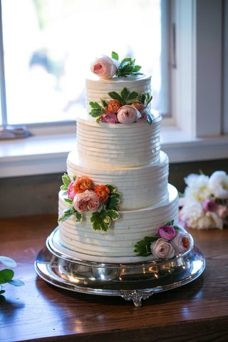 white-four-tier-cake-blush-icing-flowers-greenery-layered-ribboned