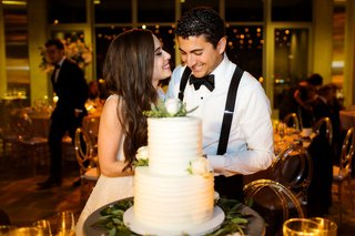 bride-and-groom-cut-into-two-layer-wedding-cake-white-with-fresh-flowers-on-top-rustic-elegant-cake