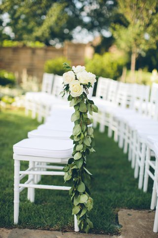 white-ceremony-chairs-adorned-with-leaf-garlands