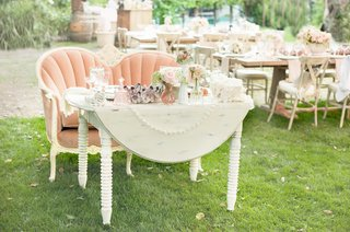 antique-white-table-with-pink-settee-bench-at-outdoor-wedding