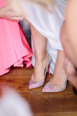 bride-puts-on-christian-louboutin-pointed-toe-clear-heels-with-rhinestone-embellishments