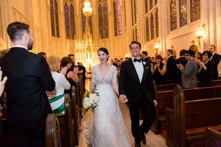 bride-in-lace-v-neck-carolina-herrera-groom-in-ralph-lauren-holds-hands-walking-up-aisle